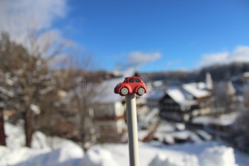 Voiture rouge de jouet devant la ville neigeuse/paysage avec le ciel bleu images stock