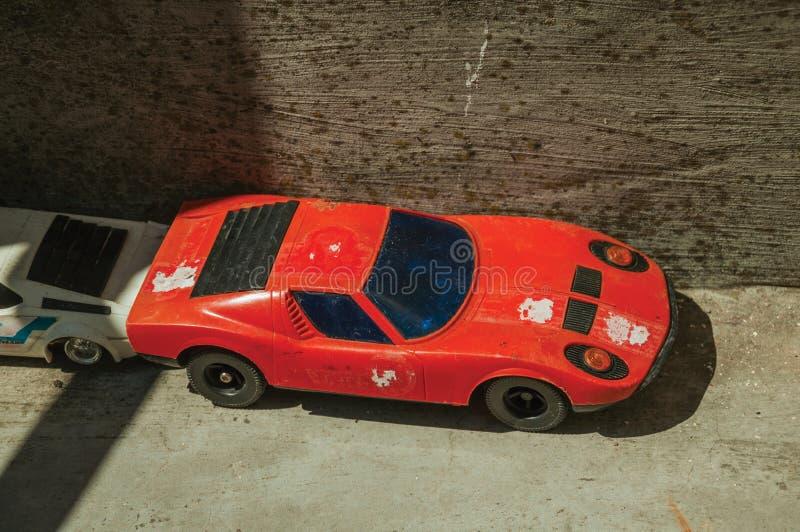 Voiture rouge de jouet faite de plastique sur le trottoir concret images libres de droits