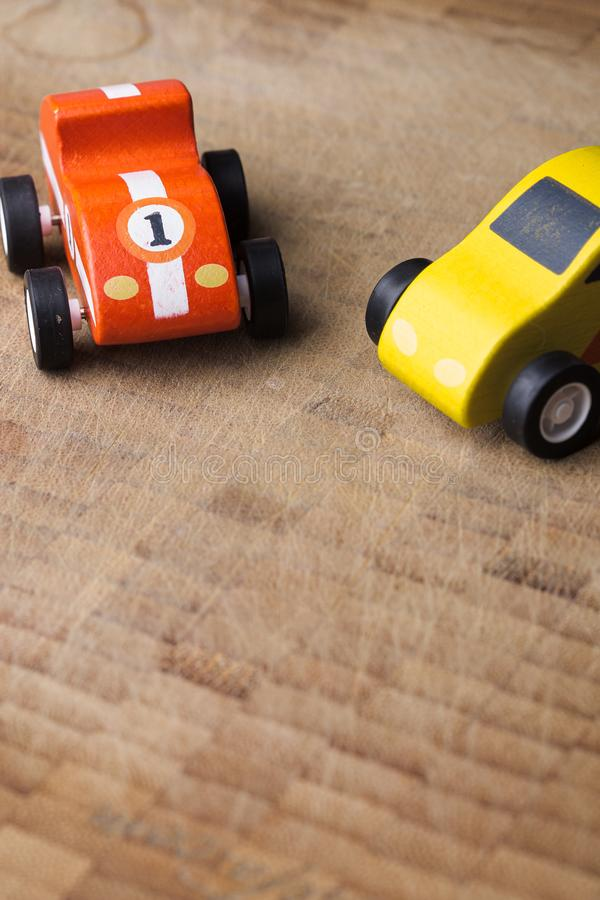 Voiture rouge et jaune de jouet de cru sur une surface en bois photos stock