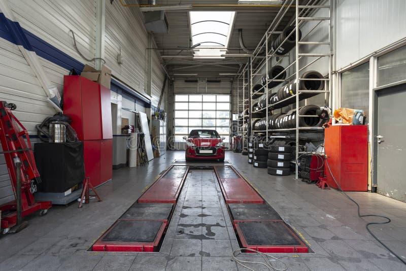 Voiture rouge pendant la révision dans un garage moderne avec un ascenseur image libre de droits