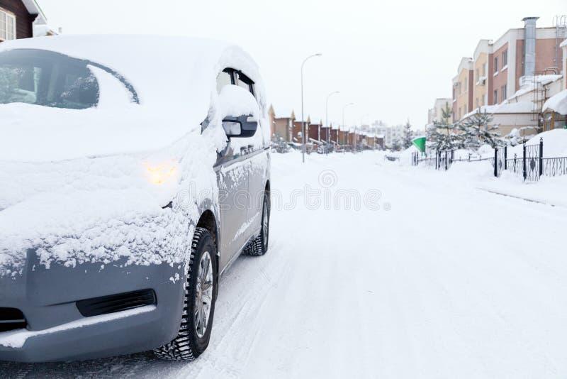 Voiture sale de minibus gris de plan rapproché couverte de neige sur le fond de ville Front View Temps neigeux de concept, chute, photographie stock libre de droits