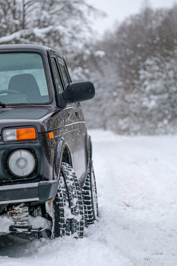 Voiture tous terrains de roues sur une route neigeuse dans l'intérieur russe Aventures d'hiver pour surmonter des secteurs de for photo stock