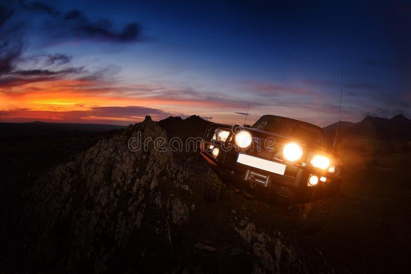 Download Voiture Tous Terrains Sur La Route De Montagne Au Coucher Du Soleil Photo stock - Image du lame, lumière: 56478776