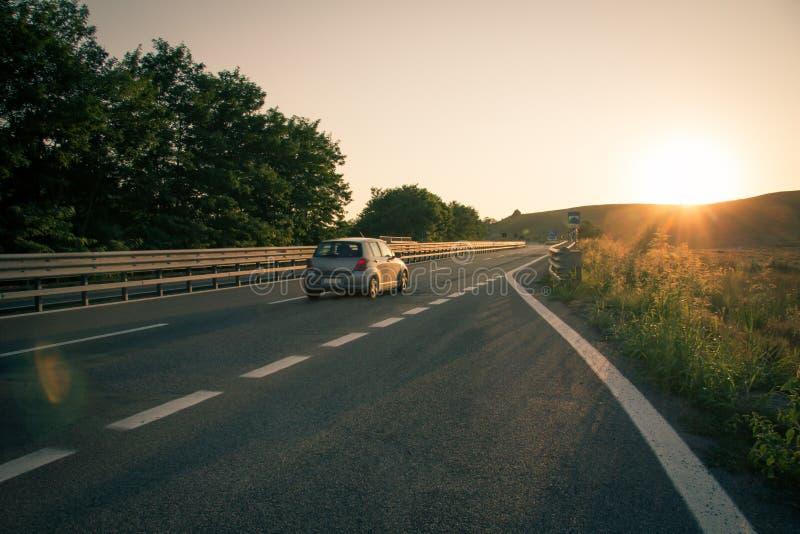Voiture vers le coucher du soleil dans l'autoroute photographie stock libre de droits