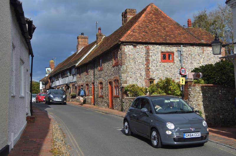 Voitures étant conduites par les rues étroites d'Alfriston pittoresque le Sussex est photographie stock libre de droits