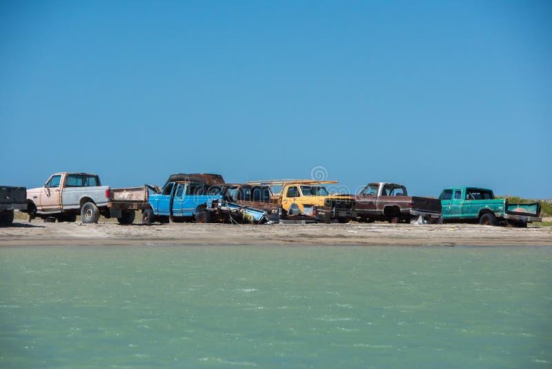 Voitures abandonnées sur la plage près de la mer photos stock