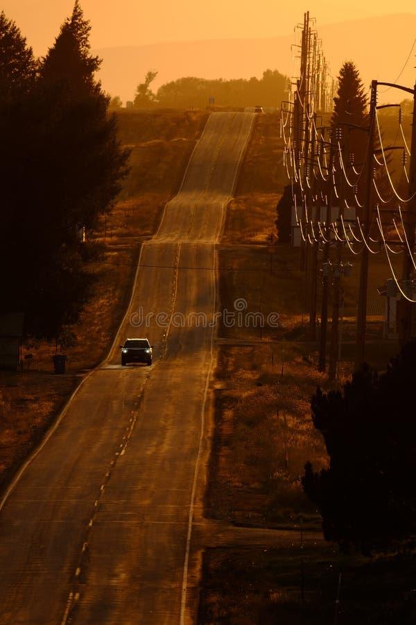 Voitures circulant sur County Road à Sunset ou Sunrise photos libres de droits