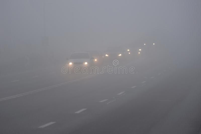 Voitures dans le brouillard Mauvais temps d'hiver et trafic d'automobile dangereux sur la route Véhicules légers en brouillard photos stock