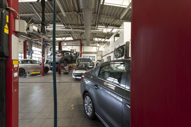 Voitures de luxe étant réparées dans un garage moderne Vue par le rouge photos stock
