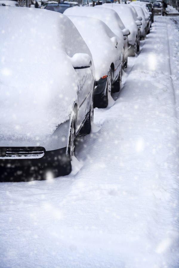 Voitures garées dans la chute de neige importante sur la rue urbaine image stock