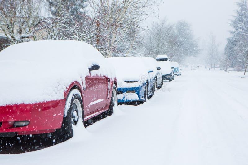 Voitures garées et emprisonnées sous une couverture profonde de neige dans la tempête inattendue de neige image libre de droits