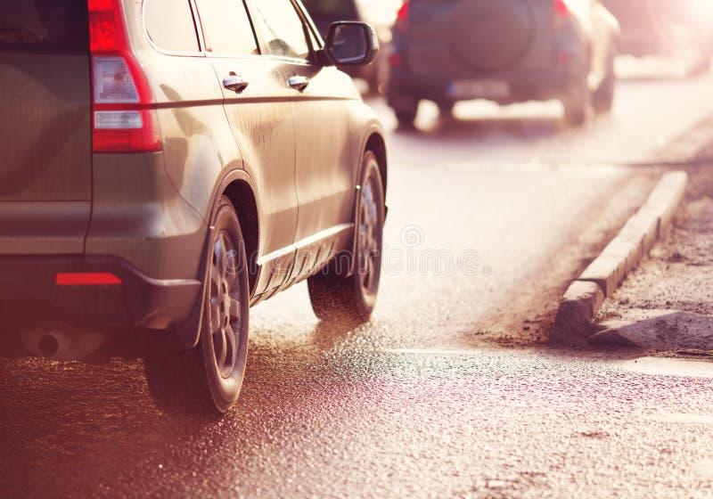 Voitures passant la route dans la ville dans le début de la matinée photographie stock