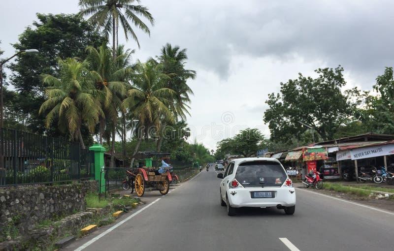 Voitures roulant sur la rue dans Jogja, Indonésie photographie stock libre de droits