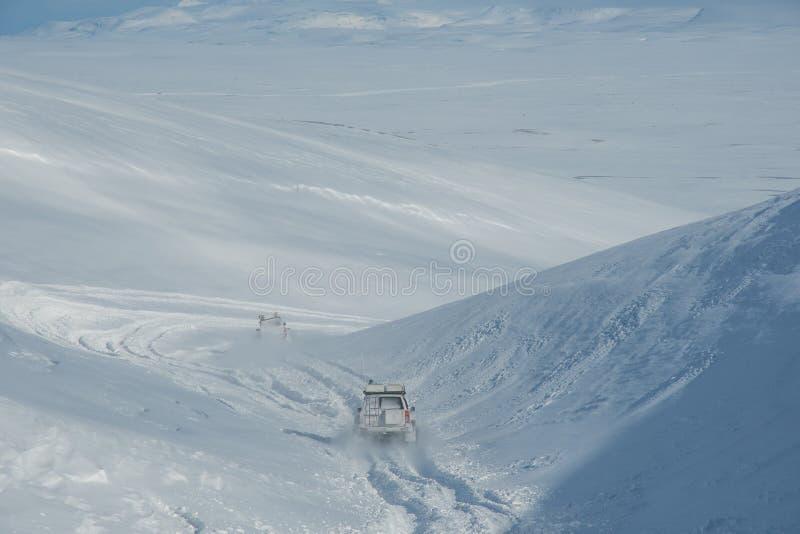 Voitures 4x4 spécialement modifiées circulant hors de la neige dans les hauts plateaux islandais photo libre de droits