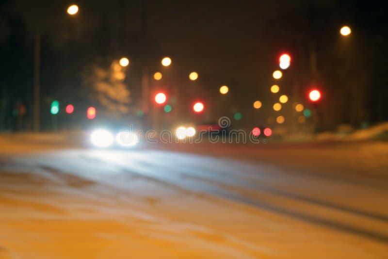 Voitures sur la route d'hiver avec la neige Le trafic de voiture dangereux en mauvais temps avec le bokeh la nuit pour employer l images libres de droits