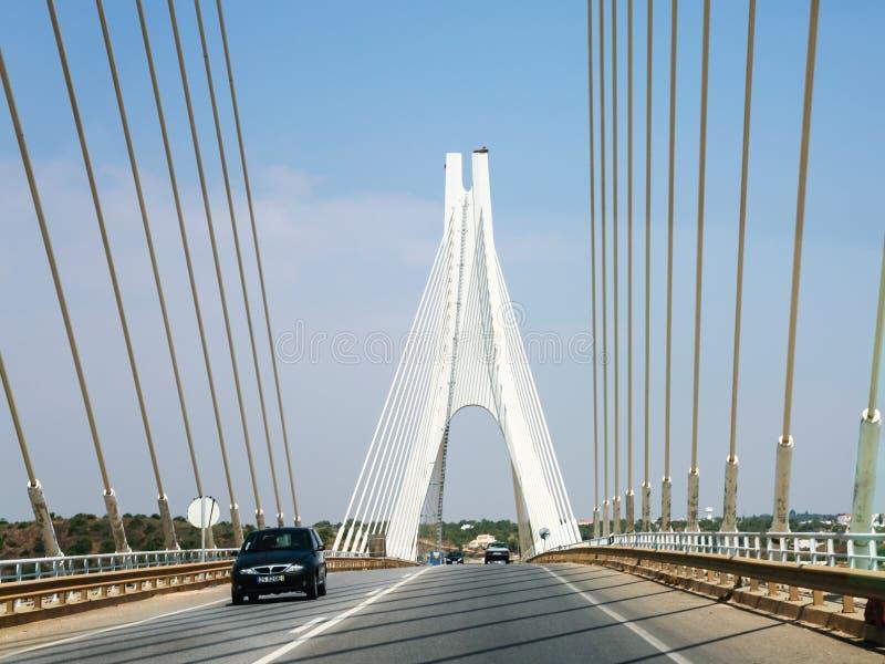Voitures sur le pont câble-resté au-dessus de la rivière d'Arade photographie stock