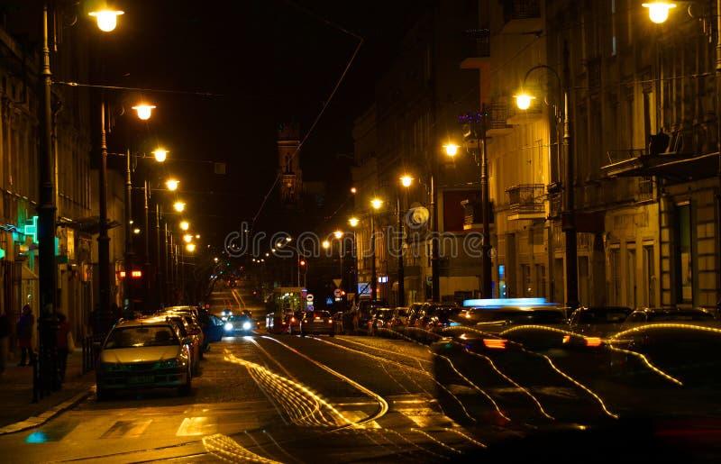 Voitures, trams, réverbères et les gens La vie de nuit de la ville photo stock