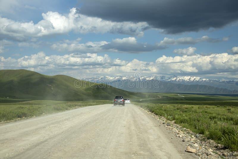 Voitures voyageant le long de la route du stresi des champs et des collines verts en direction des montagnes photographie stock
