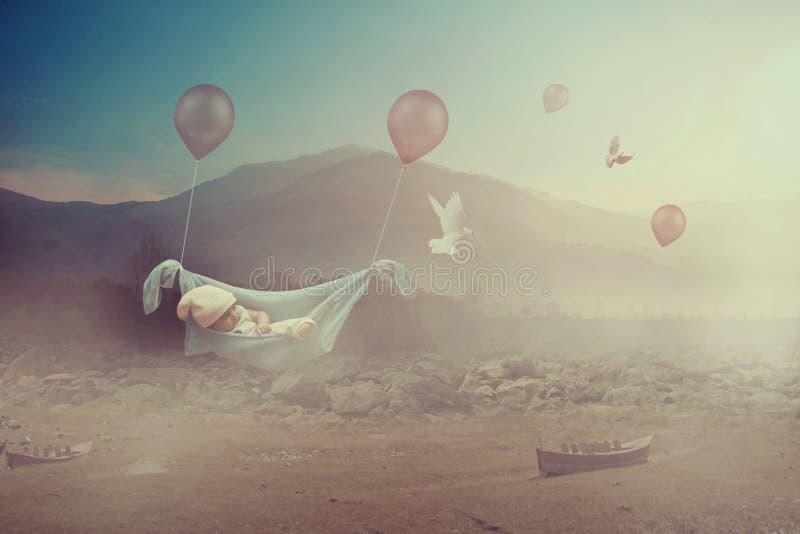 Vol adorable de bébé avec des ballons dans une vallée photographie stock libre de droits