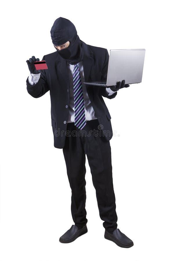 Vol avec l'ordinateur portable et la carte de crédit photo stock