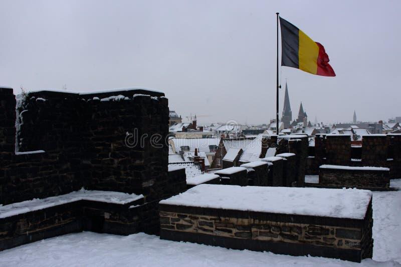 Vol belge de drapeau en vent sur le vieux toit de château avec la belle vue à la ville d'hiver Bâtiments et toits historiques de  photos libres de droits