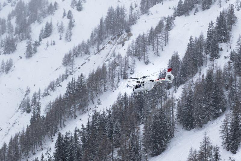 Vol blanc d'hélicoptère de délivrance en chutes de neige lourdes dans la station de sports d'hiver d'hiver dans les Alpes françai image libre de droits