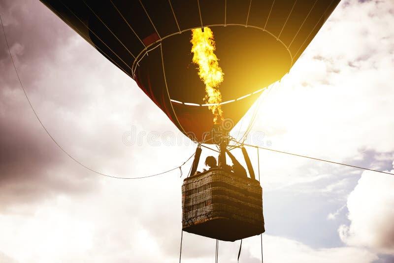 Vol chaud de ballon ? air dans un ciel nuageux au lever de soleil - image de vol de silhouette de ballon au-dessus du ciel image libre de droits