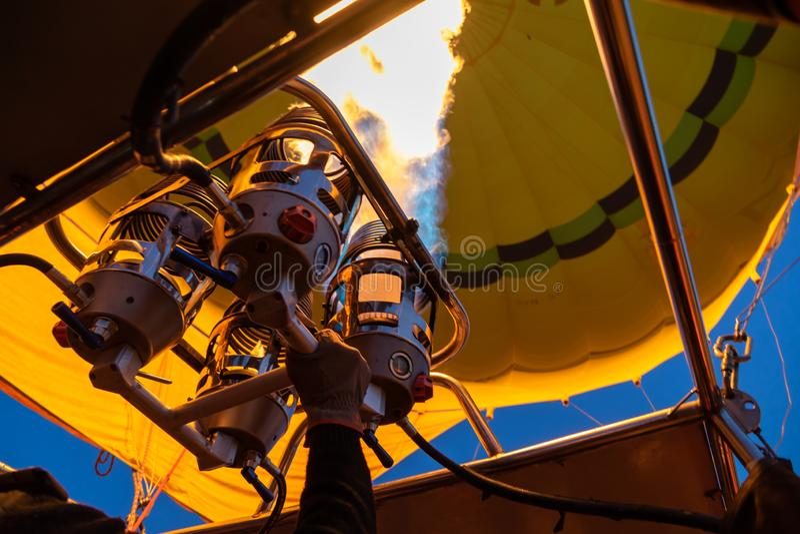 Vol chaud jaune lumineux de ballon à air avec l'équipement de la chaleur de flamme du feu de gaz par le pilote au-dessus de Cappa photos stock