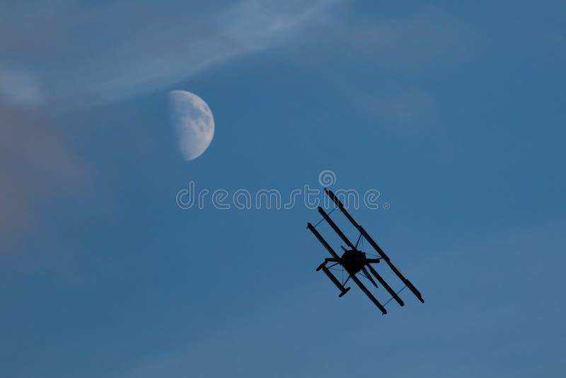 Vol classique d'avion contre la lune sur un ciel bleu dans le coucher du soleil photos stock