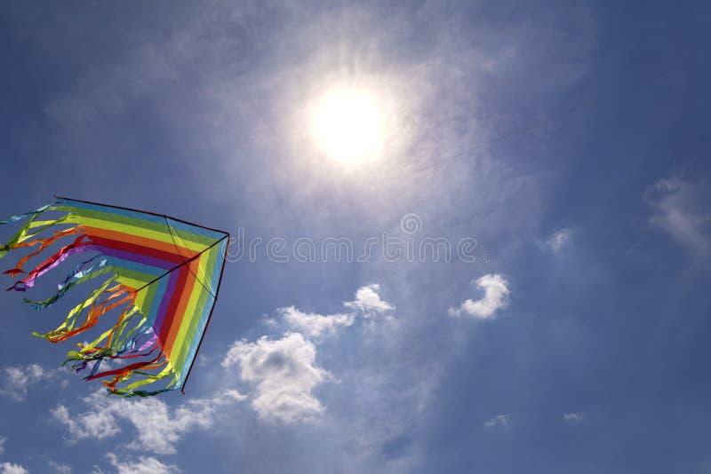 Vol coloré de cerf-volant en ciel de fond de ciel bleu Le soleil lumineux photographie stock libre de droits