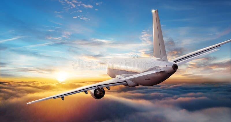 Vol commercial d'avion de ligne à réaction d'avion au-dessus des nuages au beau su photo stock