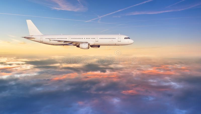 Vol d'avion de ligne à réaction d'avion au-dessus des nuages dans la belle lumière de coucher du soleil image libre de droits