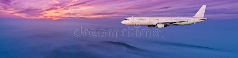 Vol d'avion de ligne à réaction d'avion au-dessus des nuages dans la belle lumière de coucher du soleil photos libres de droits