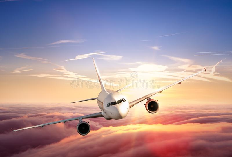 Vol d'avion de ligne à réaction d'avion au-dessus des nuages dans le beau coucher du soleil photographie stock