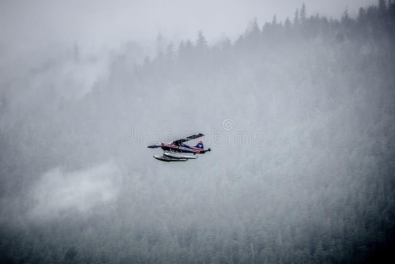 Vol d'avion de ponton d'avion d'appui vertical simple par le brouillard au-dessus d'Alask photo stock