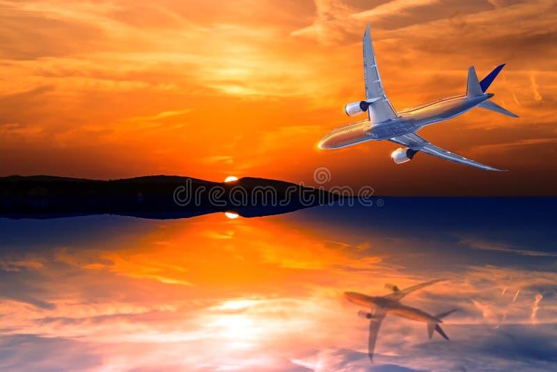 Vol d'avion vers le coucher du soleil du soleil ou lever de soleil en mer image libre de droits