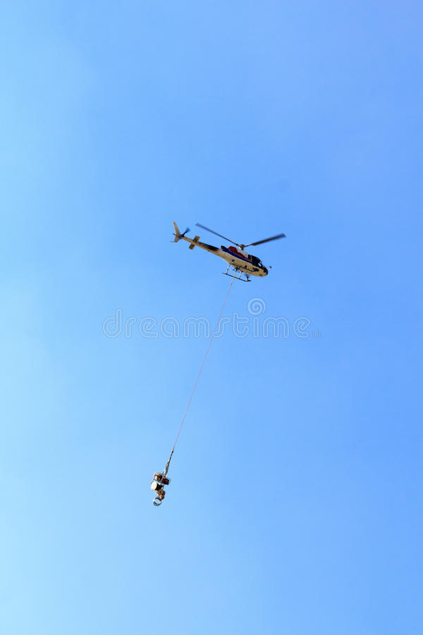 Vol d'hélicoptère de transport avec des approvisionnements image stock