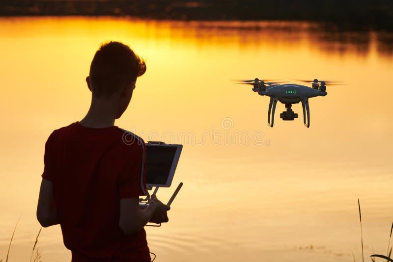Vol de bourdon pilotage d'hélicoptère au coucher du soleil de rivière image stock