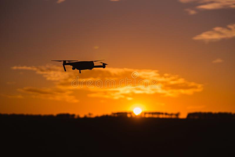 Vol de bourdon de silhouette sur le ciel de coucher du soleil de montagne avec le nuage, photographie aérienne photo stock