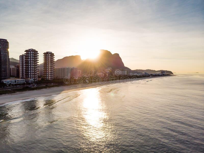 Vol de bourdon vers la plage de Barra da Tijuca tandis que filmer ondule se briser sur la plage pendant le lever de soleil, avec  photographie stock