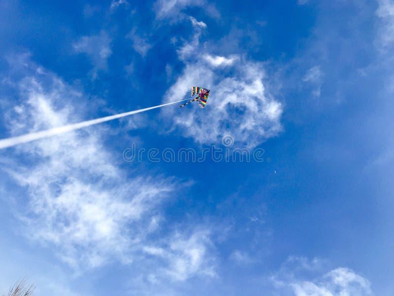 Vol de cerf-volant dans un ciel bleu avec un crâne effrayant de nuage photographie stock