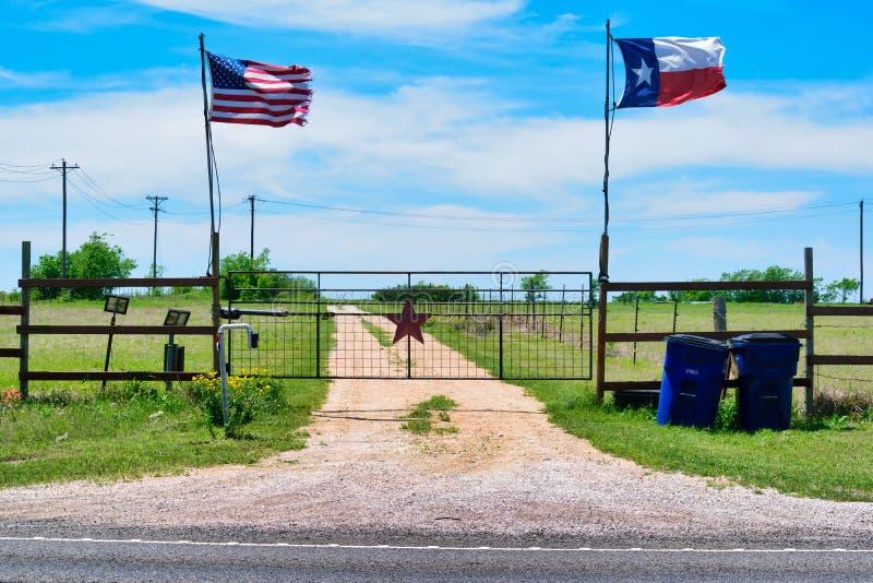Vol de drapeaux d'état d'Américain et de Texas près de la porte de campagne, étoile rustique du Texas avec la route à la maison s photographie stock libre de droits