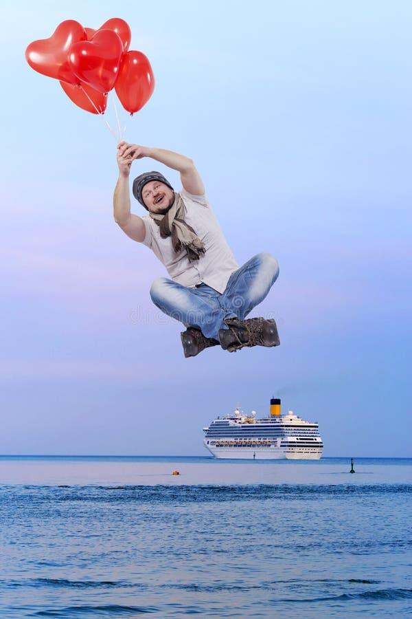 Vol de jeune homme sur des ballons avec le bateau de croisière à l'arrière-plan photos stock
