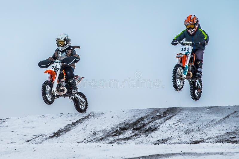 Vol de moto de deux cavaliers de garçons après avoir sauté par-dessus la montagne photos libres de droits