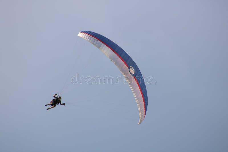 Vol de parapentisme dans le ciel photo stock