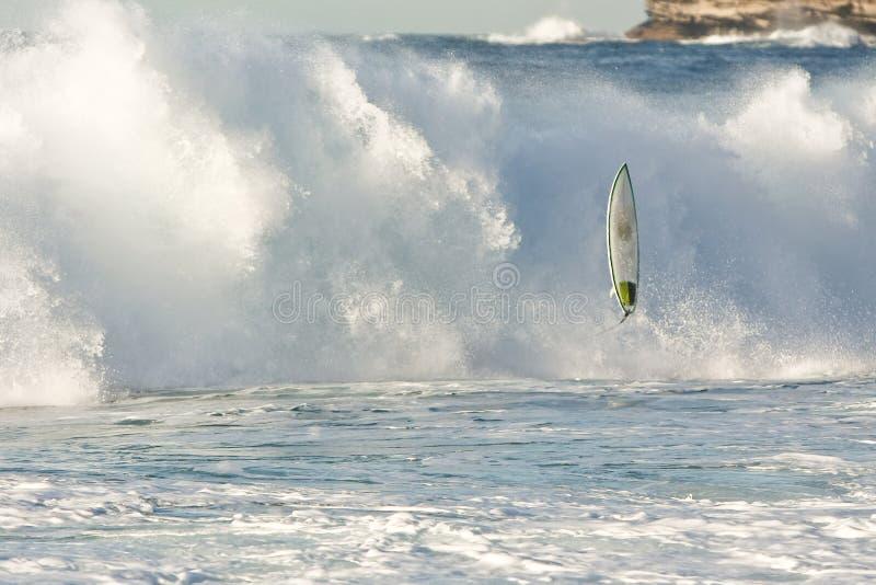 Vol de planche de surfing devant l'onde de rupture photographie stock libre de droits