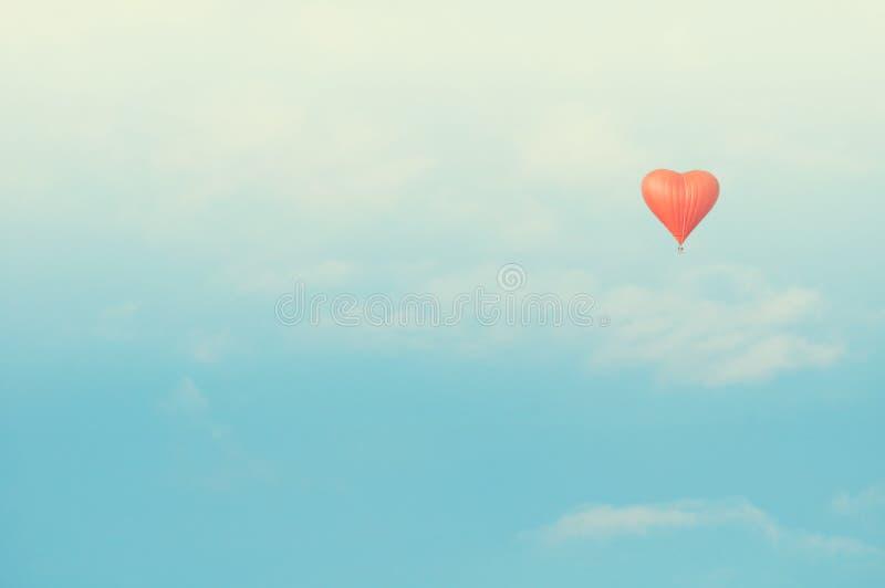 Vol en forme de coeur rouge de ballon dans le ciel ensoleillé Le vintage modifie la tonalité la correction photos libres de droits
