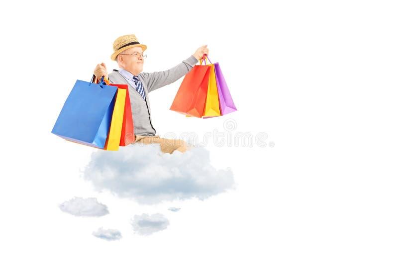Vol heureux d'homme supérieur sur des nuages et des sacs à provisions de participation photo libre de droits