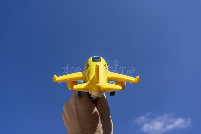 Vol jaune d'avion de jouet dedans au beau ciel bleu, l'espace négatif, concept de partir en vacances magiques photographie stock