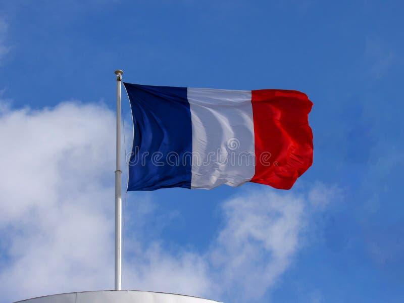 Vol matériel de drapeau de tissu tricolore français dans le fort vent avec l'espace de copie avec le fond de ciel bleu photos libres de droits